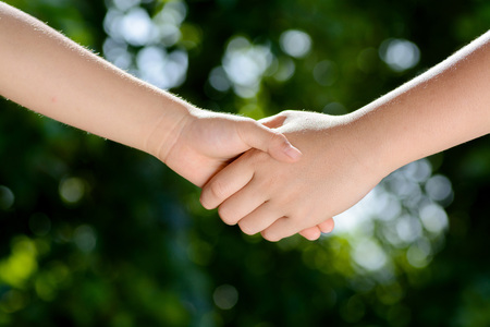 Close up two boy hands hold together on green bokeh background from tree leaf 版權商用圖片 - 47360059