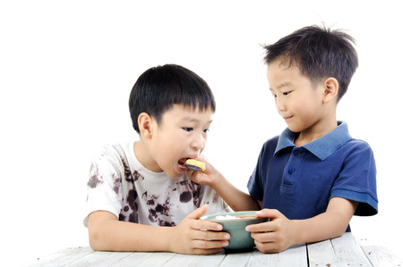 Young asian boy in white dirty shirt eat rice and fried egg from another younger boy on white background. Give and take concept