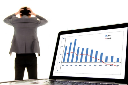 Focus on laptop monitor showing decline graph loss sales and profit, out focus headache man in suit look unhappy. Fail business concept.