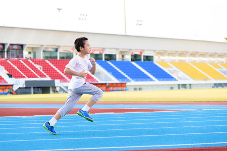 alone boy: Young Asian boy running on blue track in the stadium during day time to practice himself.