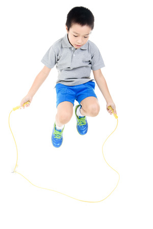 Young asian boy excercise with yellow rubber rope jumping on white background