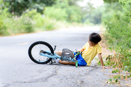 road bike: Young Asian boy got accident and fall from the bicycle and feel pain. Transportation and safety concept.
