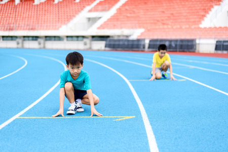 Young Asian boy prepare to start running with another boy on blue track in the stadium during day time to practice himself.