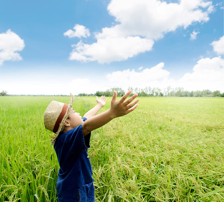 children learning: Young Asian boy in thai traditional blue shirt and straw hat feeling relax on the rice field be fore harvesting. under blue sky white cloud.
