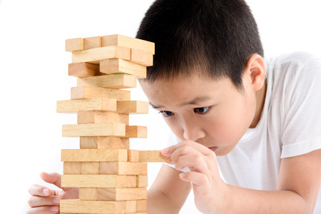 Young Asian boy try to build wooden block tower. Banque d'images