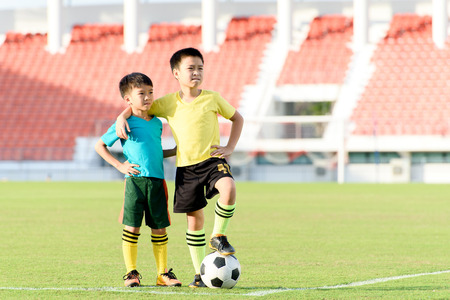 football play: Two Young Asian boy stand in the grass football field in the stadium during summer. Stock Photo
