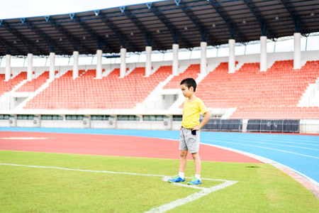 sports and recreation: Young Asian boy standing on green football field in stadium during day time and feel relax. Stock Photo