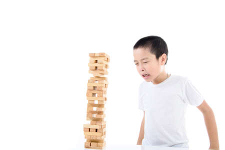 succession: Young Asian boy try to build wooden block tower. Stock Photo