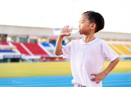 若いアジアの男の子は、スタジアムでのスポーツ後プラスチック ボトルから新鮮な水を飲みます。
