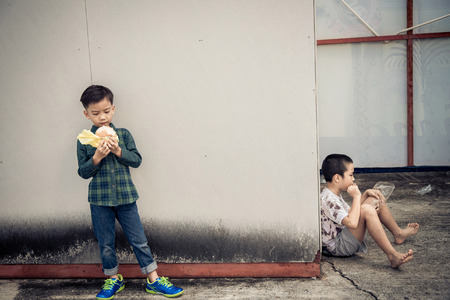 rich people: Sepia dark color tone. Younger Asian boy eat burger but poor boy eat chickent grill from bamboo stick at the corner of old building. Poor and hungry concept.
