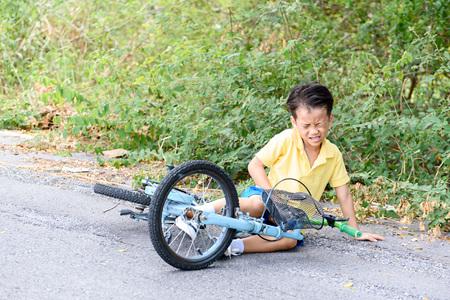 アジアの若い男の子は事故し自転車から落ちるし、痛みを感じる。輸送と安全性の概念。 写真素材