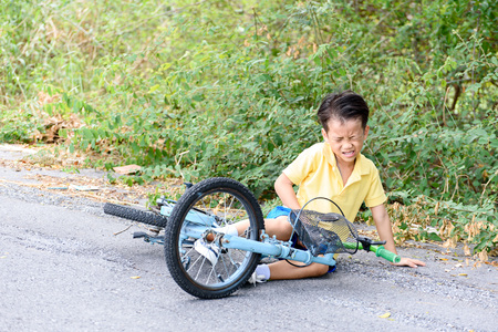Young Asian boy got accident and fall from the bicycle and feel pain. Transportation and safety concept. Reklamní fotografie - 52946690