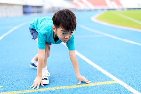 젊은 아시아 소년은 자신을 연습 낮 시간 동안 경기장에 블루 트랙에서 실행을 시작하기 위해 준비합니다.