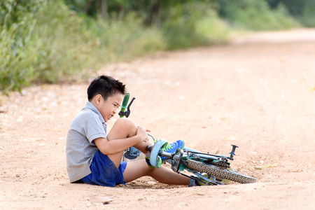 sport bike: Young Asian boy got accident and fall from the bicycle and feel pain. Transportation and safety concept.