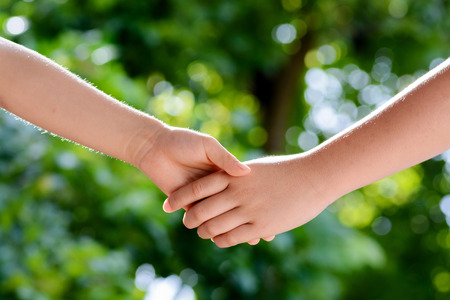 shaking out: Close up two boy hands hold together on green bokeh background from tree leaf Stock Photo