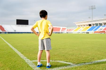 balones deportivos: El muchacho asi�tico joven que se coloca en campo de f�tbol verde en el estadio durante el d�a y sentir relajarse. Foto de archivo