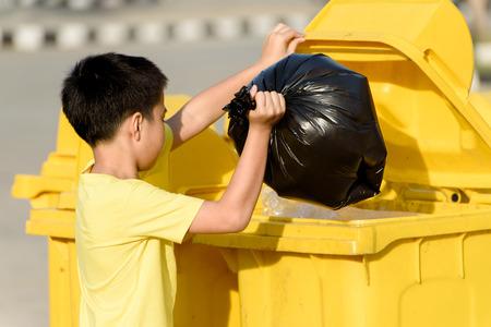 Junger asiatischer Junge carry Müll in Plastikbeutel in der gelben Tonne unter dem Sonnenlicht beseitigen
