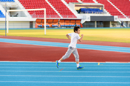 Young Asian boy running on blue track in the stadium during day time to practice himself. Reklamní fotografie - 52949496