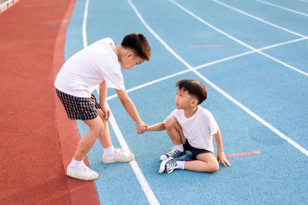 El muchacho asiático joven da la mano para ayudar a niño accidentado durante la carrera en la pista azul.