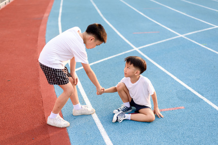 help: Young asian boy give hand to help accidented boy during running on the blue track.