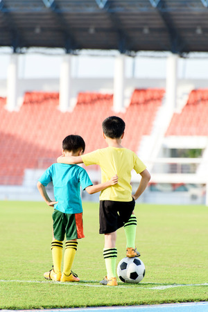 Two Young Asian boy stand in the grass football field in the stadium during summer. 版權商用圖片