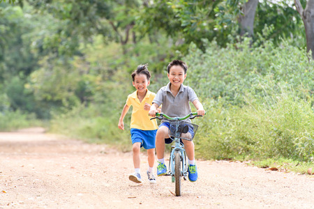bicicleta: El muchacho asiático joven montar una bicicleta azul en el camino de piedra con su hermano al lado del árbol y la hierba en verano con luz del sol caliente.