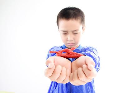 Boy Hände in der blauen Jacke dicht sind durch rote Nylonseil auf weißem Hintergrund. Freiheit Konzept. Standard-Bild
