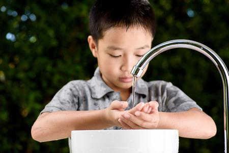 Close up kid hand under the brand new faucet. 版權商用圖片