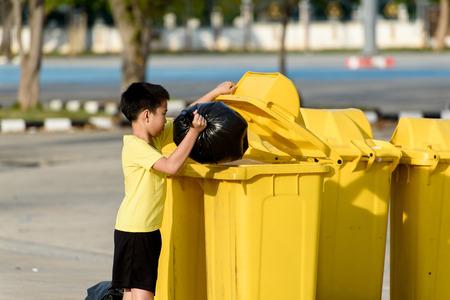 日光の下で黄色の箱の中のビニール袋でアジアの若い男の子を運ぶゴミを排除します。 写真素材