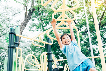 Vintage color tone, Young asian boy hang the yellow bar by his hand to exercise at out door playground under the big tree. Imagens