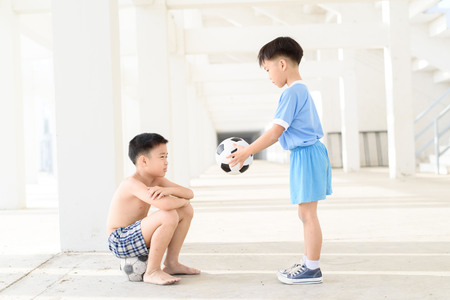 Young Asian boy give football to another boy in white building.