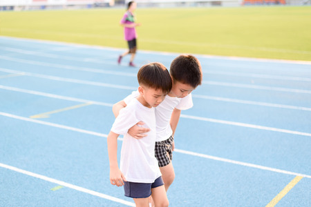 Boy help each other to run on the running track. Stock Photo