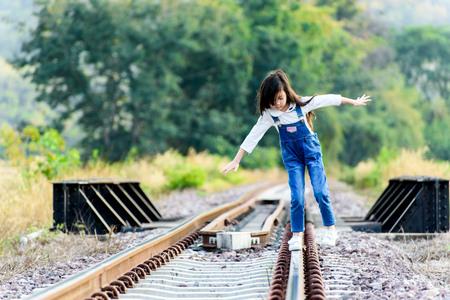 森の背景では、鉄道の上を歩く若いアジアのタイの女の子