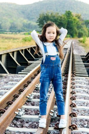 forest railway: Young asian Thai girl, walking on the railway on the forest background