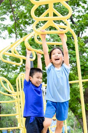Junge asiatische Junge den gelben Balken von seiner Hand hängen an Tür Spielplatz unter dem großen Baum zu trainieren.