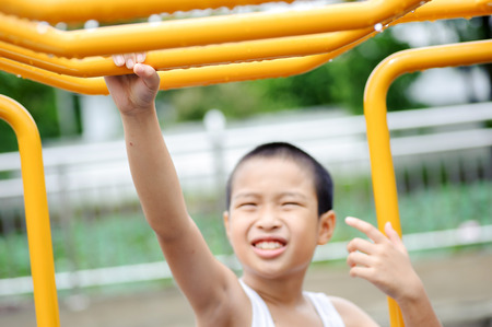 out door: Young asian boy hang the yellow bar by his hand to exercise at out door playground