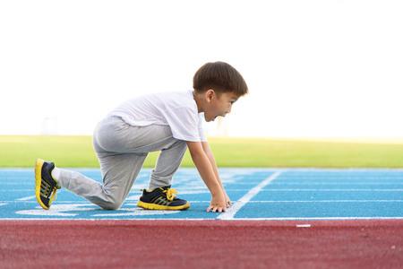 Jeune garçon asiatique courir sur piste bleue dans le stade pendant la journée pour se pratiquer. Banque d'images - 53854640