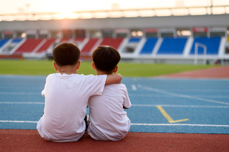 Two asian boy sit beside the blue running track and look to the stadium and sunset.