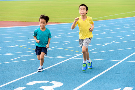 Young Asian boy running on blue track in the stadium during day time to practice himself. Imagens - 53854626