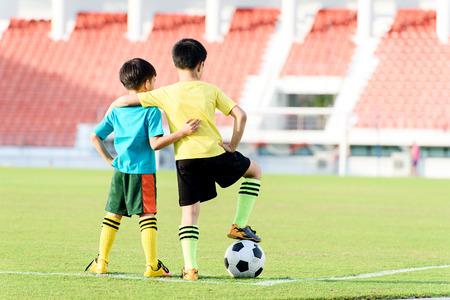 Twee jonge Aziatische jongen staan op het voetbalveld gras in het stadion tijdens de zomer.