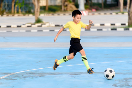 Young Asian boy play football on the blue concrete floor during summer.