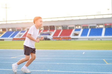 during the day: Young Asian boy running on blue track in the stadium during day time to practice himself.
