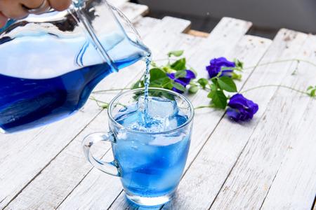 花と木のテーブル上あふれるカップに氷と蝶エンドウ豆ジュースを提供します。