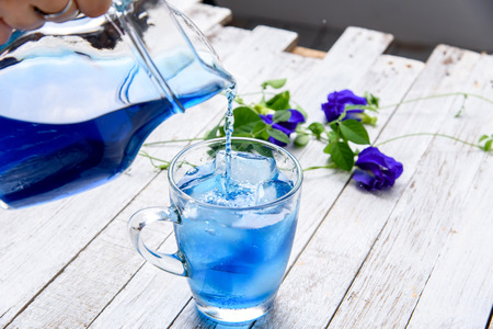 Butterfly pea juice with ice in trasparent cup serve on wooden table with flower. Imagens
