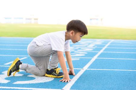pista de atletismo: El muchacho asiático joven que se ejecuta en la pista azul en el estadio durante el día para practicar él mismo.