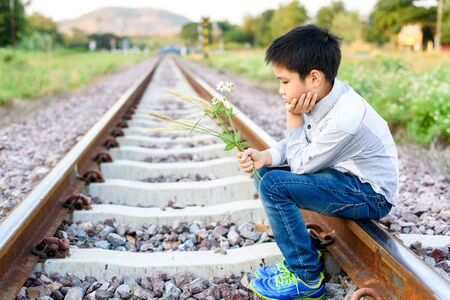 Young asian boy sit and wait on the railway alone.