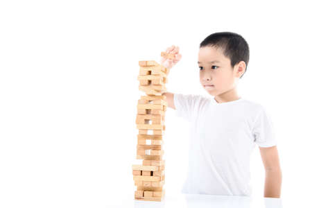 failed strategy: Young Asian boy try to build wooden block tower. Stock Photo