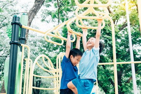 Vintage color tone, Young asian boy hang the yellow bar by his hand to exercise at out door playground under the big tree. 版權商用圖片 - 53854575