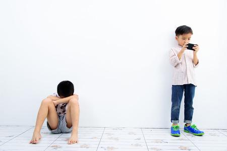 niños pobres: Juego del niño más joven asiática teléfono inteligente, otro pobre chico se ve infeliz y solitaria en la pared blanca. Concepto de red social.