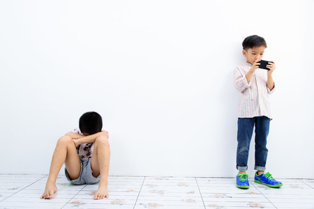 Younger Asian boy play smartphone, another poor boy looks unhappy and lonely at the white wall. Social network concept.